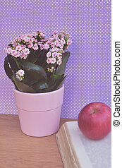 Manzana en el libro y hermosas flores