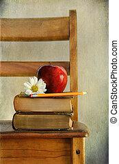 Manzana y libros en la silla de la vieja escuela