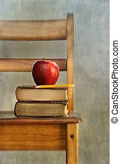 Manzana y libros viejos en la silla de la escuela
