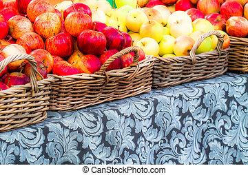 Manzanas frescas en canastas en el mercado de un granjero