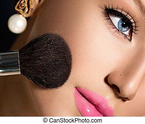 Maquillaje aplicando el primer plano. Un cepillo cosmético para maquillaje