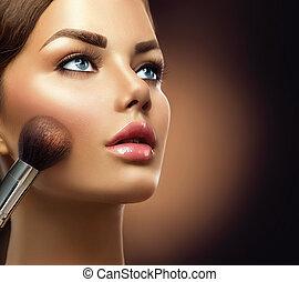 Maquillaje. Una chica modelo de belleza aplicando maquillaje