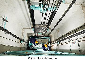Maquinistas ajustando el ascensor en el elevador