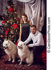 Marido y mujer con perros blancos en el árbol de Navidad