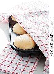 Masa de levadura en una bandeja de magdalenas con una toalla blanca y roja sobre fondo blanco como una toma de estudio