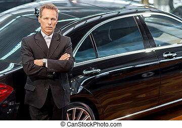 Me encantan los coches de lujo. La mejor vista de un hombre de pelo gris seguro con ropa formal inclinado hacia el coche y mirando a la cámara