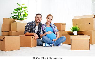 Me mudo a un nuevo apartamento. Esposa embarazada y marido de familia con cajas de cartón