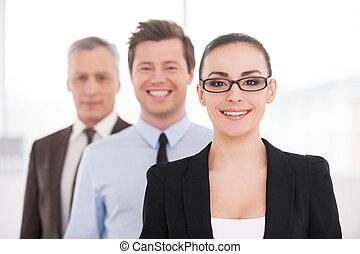 Me siento confiado con su equipo. Hermosa joven mujer de traje formal y gafas mirando a la cámara y sonriendo mientras sus colegas de pie en una fila detrás de ella