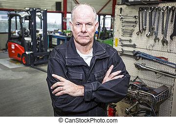 Mecánico en el garaje de la carretilla elevadora