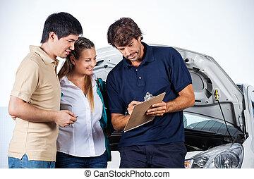 Mecánico explicando documentos a la pareja