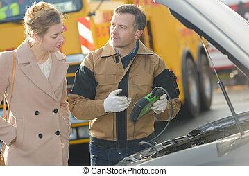 Mecánico hablando con una clienta sobre el motor del coche