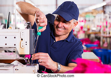 Mecánico senior reparando máquinas de costura industrial