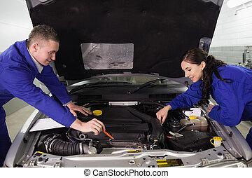 Mecánicos mirando un motor de coche