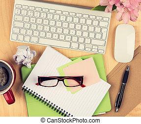 Mesa de oficina desordenada con bloc de notas, ordenador, gafas de lectura y taza de café. Vista desde arriba con espacio de copia