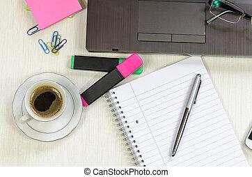 Mesa de oficina desordenada con cuaderno, bloc y café