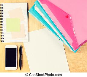 Mesa de oficina desordenada con smartphone, bloc de notas y carpetas de relleno. Vista desde arriba con espacio de copia