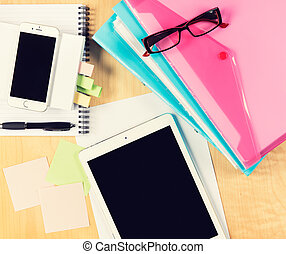 Mesa de oficina desordenada con tablet digital, smartphone, gafas de lectura, bloc de notas y carpetas de relleno. Vista desde arriba con espacio de copia