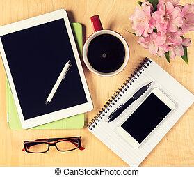 Mesa de oficina desordenada con tableta digital, smartphone, gafas de lectura, bloc y taza de café. Vista desde arriba con espacio de copia