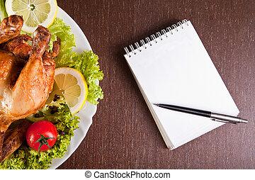 Mesa de restaurante con pollo asado, cuaderno y bolígrafo