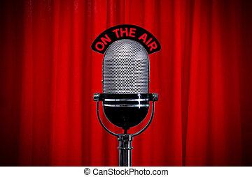 Micrófono en el escenario con foco en la cortina roja