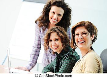 Mientras nos reunimos, un grupo de mujeres jóvenes trabajando juntas en la mesa