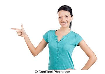 ¡Mira esto! Una joven hermosa señalando y sonriendo mientras está aislada en blanco