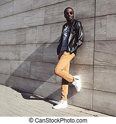 Moda de la calle, un joven africano con gafas de sol y una chaqueta de cuero negra en el fondo de la ciudad