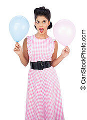 Modelo de cabello negro sosteniendo globos