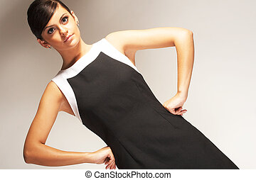 Modelo de moda posado en un fondo claro de vestido negro