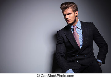 Modelo de moda sentado en traje mira hacia otro lado