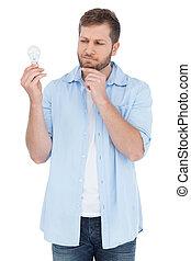 Modelo escéptico sosteniendo una bombilla