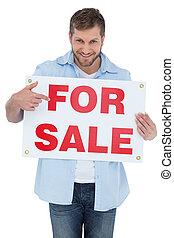 Modelo sonriente sosteniendo un cartel de venta