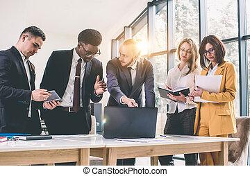 moderno, computador portatil, diverso, luz, tablet., interior, gente, grupo, trabajando, ocupado, poniendo común, multiétnico, concepto, inicio, reunión equipo, oficinacomercial