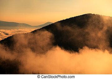 Montaña en nubes y colinas en niebla