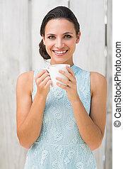 Morena con estilo sosteniendo una taza