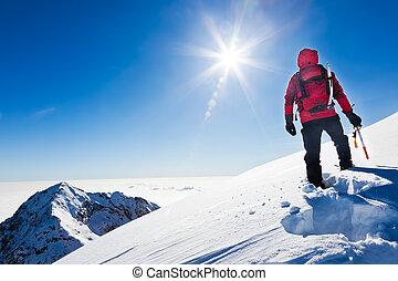 Mountaineer llega a la cima de una montaña nevada en un día soleado de invierno. Alpes occidentales, biella, Italia.