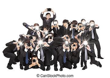 Muchos fotógrafos con cámara apuntando hacia ti y aislados en blanco