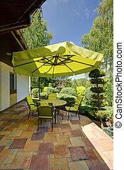 Muebles de jardín verdes con sombreado