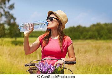 Mujer activa con bicicleta bebiendo agua fría