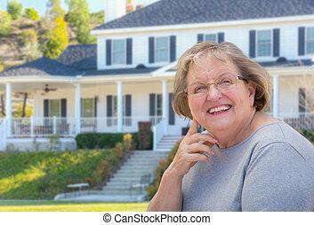 Mujer adulta mayor en frente de la casa
