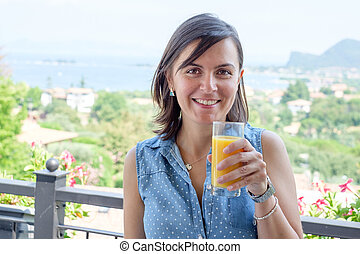 Mujer alegre bebiendo un vaso de jugo de naranja