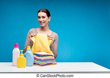 Mujer alegre mostrando ropa limpia en la mesa con detergentes