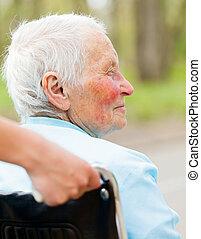 Mujer anciana en silla de ruedas al aire libre