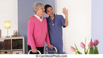 Mujer anciana feliz paciente hablando con enfermera asiática