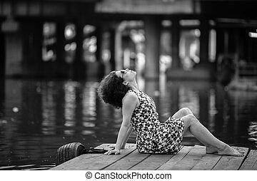 Mujer asiática en un muelle de río de madera
