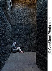 Mujer asustada y loca escondida en un rincón de un edificio antiguo.