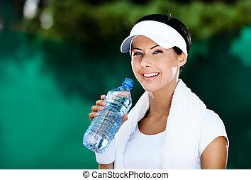 Mujer atlética con botella de agua
