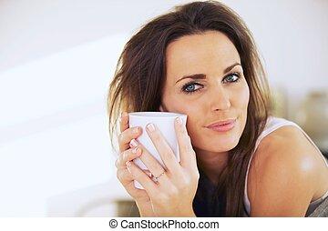 Mujer atractiva sosteniendo una taza cerca de su cara