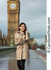Mujer bebiendo café hablando por teléfono celular, Big Ben, Londres, Inglaterra