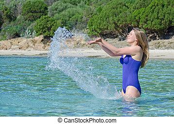 Mujer bonita salpicando agua en el mar.